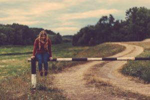 Jeune fille sur une barrière qui bloque un chemin de campagne