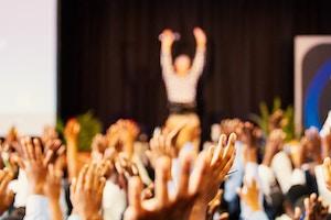 Personnes et animateur conférence levant la main