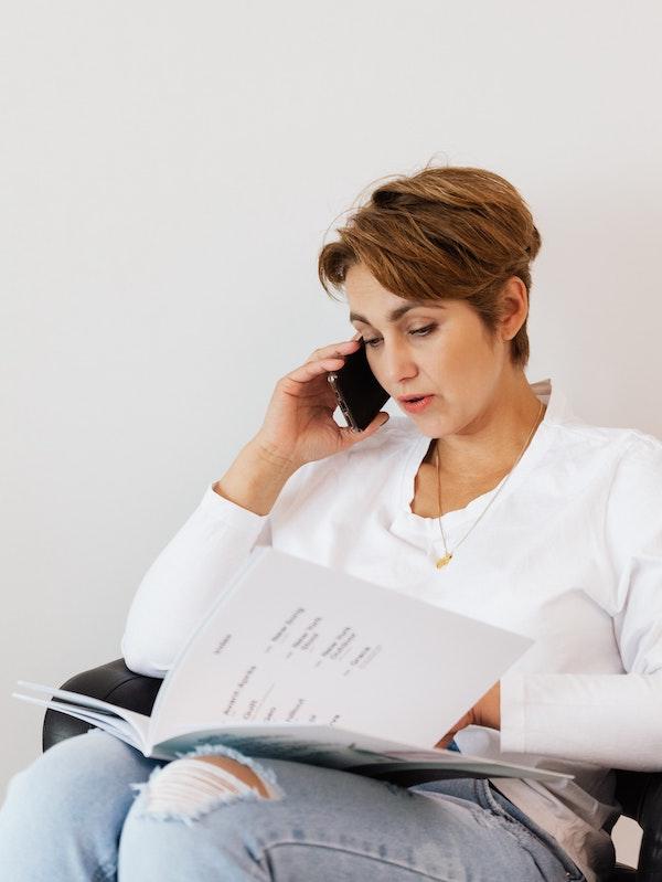 Femme au téléphone consultant le catalogue de formations de Madame Pitch